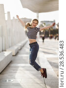 Купить «Funny blonde woman jumping in urban background. Beautiful young girl wearing striped t-shirt and blue jeans in the street. Pretty russian female with pigtail.», фото № 28536483, снято 24 января 2017 г. (c) Ingram Publishing / Фотобанк Лори