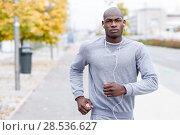 Купить «Attractive black man running in urban background. Male doing workout outdoors. Guy listening to music with white headphones», фото № 28536627, снято 20 ноября 2016 г. (c) Ingram Publishing / Фотобанк Лори
