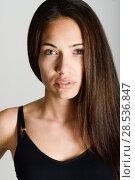 Купить «Beautiful young woman without make-up. Beautiful girl with green eyes, model of fashion wearing black tank top on white background.», фото № 28536847, снято 30 января 2016 г. (c) Ingram Publishing / Фотобанк Лори