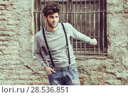 Купить «Portrait of young man wearing suspenders in urban background», фото № 28536851, снято 8 апреля 2014 г. (c) Ingram Publishing / Фотобанк Лори