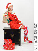 Купить «Beautiful happy blonde woman in Santa Claus clothes and striped socks sitting on a locker. Young funny girl with blue eyes carrying a sack of santa claus, isolated on white», фото № 28536927, снято 23 августа 2017 г. (c) Ingram Publishing / Фотобанк Лори