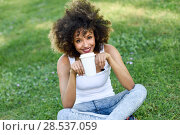 Купить «Beautiful young African American woman with afro hairstyle. Girl drinking coffee with a take away glass in park sitting on grass wearing casual clothes smiling.», фото № 28537059, снято 14 июня 2016 г. (c) Ingram Publishing / Фотобанк Лори