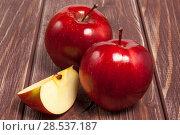 Купить «Долька яблока и два целых яблока на деревянном фоне», фото № 28537187, снято 15 ноября 2017 г. (c) Сергей Васильев / Фотобанк Лори
