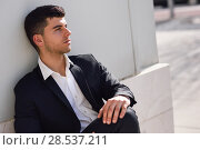 Купить «Young businessman near a modern office building wearing black suit and white shirt sitting on the floor. Man with blue eyes in urban background», фото № 28537211, снято 4 марта 2015 г. (c) Ingram Publishing / Фотобанк Лори