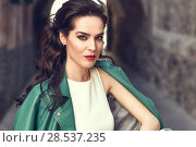 Купить «Young brunette woman, model of fashion, wearing green modern jacket. Pretty caucasian girl with long wavy hairstyle. Female with red lips in urban background.», фото № 28537235, снято 11 марта 2017 г. (c) Ingram Publishing / Фотобанк Лори