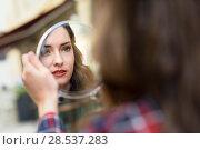 Купить «Portrait of young woman looking at herself in a little mirror in urban background», фото № 28537283, снято 26 апреля 2016 г. (c) Ingram Publishing / Фотобанк Лори