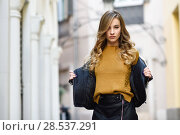 Купить «Blonde woman in urban background. Beautiful young girl wearing black leather jacket and mini skirt standing in the street. Pretty russian female with long wavy hair hairstyle and blue eyes.», фото № 28537291, снято 24 января 2017 г. (c) Ingram Publishing / Фотобанк Лори