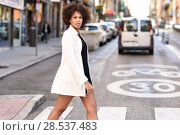 Купить «Young black woman with afro hairstyle walking on a crosswalk in an urban street. Mixed girl wearing white jacket and black dress with city background.», фото № 28537483, снято 10 декабря 2016 г. (c) Ingram Publishing / Фотобанк Лори