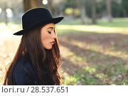 Купить «Portrait of thoughtful woman sitting alone outdoors wearing hat. Nice backlit with sunlight», фото № 28537651, снято 12 января 2016 г. (c) Ingram Publishing / Фотобанк Лори