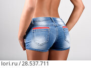 Купить «Woman wearing denim shorts with a beautiful waist. Studio shot», фото № 28537711, снято 10 февраля 2015 г. (c) Ingram Publishing / Фотобанк Лори