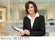 Купить «Portrait of a business woman in an office. Businesswoman writting with a folder in her hands in a modern office.», фото № 28537771, снято 14 января 2014 г. (c) Ingram Publishing / Фотобанк Лори