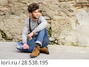 Купить «Portrait of young man wearing suspenders sitting on the floor in urban background», фото № 28538195, снято 8 апреля 2014 г. (c) Ingram Publishing / Фотобанк Лори