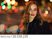 Купить «Beautiful young girl wearing black jacket walking in the street with defocused city lights at the background. Pretty russian female with long wavy hair hairstyle. Blonde woman in urban background.», фото № 28538235, снято 24 января 2017 г. (c) Ingram Publishing / Фотобанк Лори