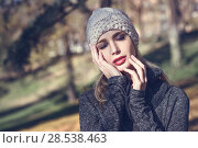 Купить «Young blonde woman standing in a park with autumn colors. Beautiful girl wearing winter gray dress and wool cap. Female with straight hair and eyes closed with dark eyeshadow.», фото № 28538463, снято 11 декабря 2016 г. (c) Ingram Publishing / Фотобанк Лори