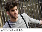 Купить «Portrait of young man wearing suspenders in urban background», фото № 28538495, снято 8 апреля 2014 г. (c) Ingram Publishing / Фотобанк Лори