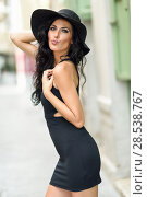 Купить «Brunette woman, model of fashion, wearing black seductive dress and sun hat in the street. Young girl with curly hairstyle blowing a kiss in urban background», фото № 28538767, снято 7 июля 2016 г. (c) Ingram Publishing / Фотобанк Лори