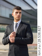 Young businessman near a modern office building wearing black suit and tie. Man with blue eyes. Стоковое фото, фотограф Javier Sánchez Mingorance / Ingram Publishing / Фотобанк Лори