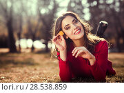 Купить «Portrait of young woman rest in the park with a dandelion in her hair, lying on the grass», фото № 28538859, снято 10 марта 2015 г. (c) Ingram Publishing / Фотобанк Лори