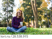 Купить «Young happy Woman in checkered shirt and blue jeans with toothy Smile and sunglasses. Blonde girl drinking coffee in park sitting on grass wearing casual clothes smiling», фото № 28538915, снято 14 ноября 2015 г. (c) Ingram Publishing / Фотобанк Лори
