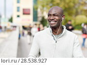 Black young man with a smartphone in his hand in urban background. Young african guy with shaved head wearing casual clothes and white headphones. Стоковое фото, фотограф Javier Sánchez Mingorance / Ingram Publishing / Фотобанк Лори