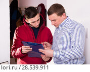 Купить «Guy is working as a courier and delivering order for adult male», фото № 28539911, снято 5 февраля 2018 г. (c) Яков Филимонов / Фотобанк Лори