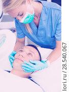 Купить «Female doctor is doing massage of skin of face to client», фото № 28540067, снято 20 октября 2018 г. (c) Яков Филимонов / Фотобанк Лори