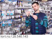 Купить «male customer choosing fishing hooks near stand in the sports shop», фото № 28540143, снято 16 января 2018 г. (c) Яков Филимонов / Фотобанк Лори