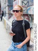 Купить «Woman using smartphones against colorful graffiti wall in New York city, USA.», фото № 28543627, снято 4 апреля 2020 г. (c) Matej Kastelic / Фотобанк Лори
