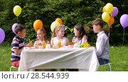 Купить «happy kids on birthday party at summer garden», видеоролик № 28544939, снято 5 июня 2018 г. (c) Syda Productions / Фотобанк Лори