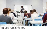 Купить «Smiling African American teacher giving presentation for students in lecture hall», видеоролик № 28546799, снято 23 мая 2018 г. (c) Яков Филимонов / Фотобанк Лори