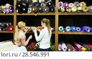 Купить «Two cheerful young female friends looking for interesting cloth in textile shop», видеоролик № 28546991, снято 28 марта 2018 г. (c) Яков Филимонов / Фотобанк Лори