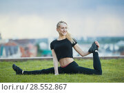 Happy young woman on the grass performs twine with the bent leg, on background cityscape. Стоковое фото, фотограф Константин Шишкин / Фотобанк Лори