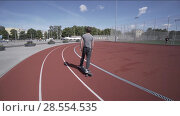 Купить «Electric Longboard summer ride on red sport stadium with playground», видеоролик № 28554535, снято 9 июня 2018 г. (c) Aleksejs Bergmanis / Фотобанк Лори