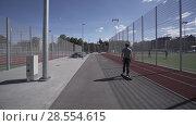 Купить «Electric Longboard summer ride on red sport stadium with playground», видеоролик № 28554615, снято 9 июня 2018 г. (c) Aleksejs Bergmanis / Фотобанк Лори