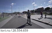 Купить «Electric Longboard summer ride on red sport stadium with playground», видеоролик № 28554659, снято 9 июня 2018 г. (c) Aleksejs Bergmanis / Фотобанк Лори