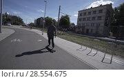 Купить «Electric Longboard man in sweatshirt and hat ride on red sport stadium with playground», видеоролик № 28554675, снято 10 июня 2018 г. (c) Aleksejs Bergmanis / Фотобанк Лори