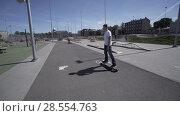 Купить «Electric Longboard man in white t-shirt and hat ride on red sport stadium with playground», видеоролик № 28554763, снято 9 июня 2018 г. (c) Aleksejs Bergmanis / Фотобанк Лори