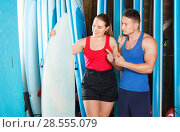 Купить «Young couple planning to surf, choosing boards and surfing suits in beach club», фото № 28555079, снято 30 апреля 2018 г. (c) Яков Филимонов / Фотобанк Лори