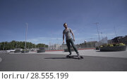 Купить «Electric Longboard summer ride on red sport stadium with playground», видеоролик № 28555199, снято 9 июня 2018 г. (c) Aleksejs Bergmanis / Фотобанк Лори