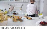 Купить «Young woman pulls out of a plate freshly cooked pancakes», видеоролик № 28556815, снято 24 марта 2019 г. (c) Константин Шишкин / Фотобанк Лори