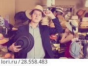 Купить «portrait of young guy try on panama at headwear store», фото № 28558483, снято 2 мая 2017 г. (c) Яков Филимонов / Фотобанк Лори