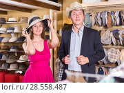 Купить «cheerful female and man choosing hats in the store», фото № 28558487, снято 2 мая 2017 г. (c) Яков Филимонов / Фотобанк Лори