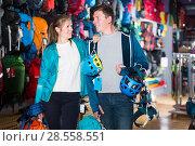 Купить «active girl and guy select gear for hiking and camping in sports shop», фото № 28558551, снято 25 октября 2017 г. (c) Яков Филимонов / Фотобанк Лори