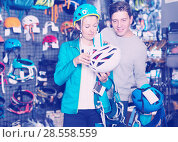 Купить «Girl and the guy choosing mountaineering equipment», фото № 28558559, снято 25 октября 2017 г. (c) Яков Филимонов / Фотобанк Лори