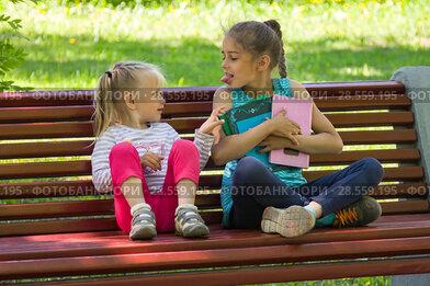 Дети ссорятся на скамейке в парке, старшая сестра не хочет делиться книжками с младшей