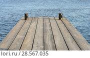 Купить «Деревянный настил из досок на фоне воды, пирс в солнечный день», видеоролик № 28567035, снято 10 июня 2018 г. (c) FMRU / Фотобанк Лори