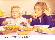 Купить «Two little girls enjoying pastry with cream», фото № 28567607, снято 14 декабря 2018 г. (c) Яков Филимонов / Фотобанк Лори