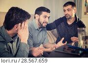 Купить «Three anxious men discussing on sofa», фото № 28567659, снято 10 января 2018 г. (c) Яков Филимонов / Фотобанк Лори