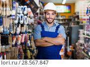Купить «Confident handyman with folded arms in paint store», фото № 28567847, снято 13 сентября 2017 г. (c) Яков Филимонов / Фотобанк Лори