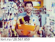 Купить «Satisfied guy handyman holding basket with tools», фото № 28567859, снято 13 сентября 2017 г. (c) Яков Филимонов / Фотобанк Лори